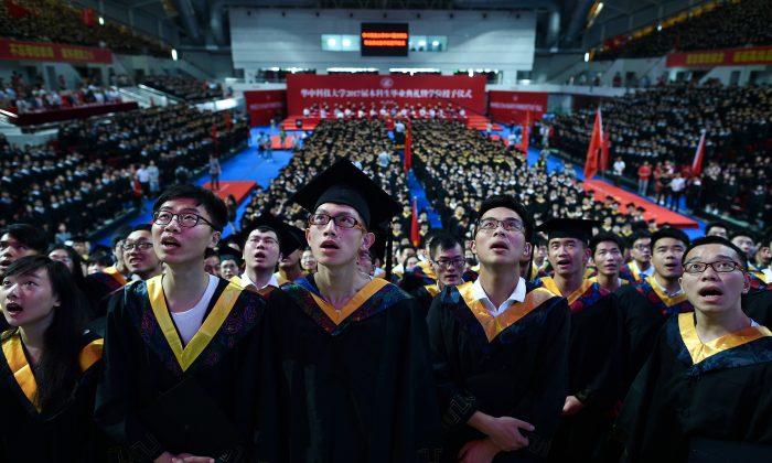 Estudiantes de la Universidad Huazhong de Ciencia y Tecnología cantan durante su ceremonia de graduación en un estadio deportivo de la ciudad de Wuhan, en la provincia central de Hubei, China, el 20 de junio de 2017. (STR/AFP/Getty Images)