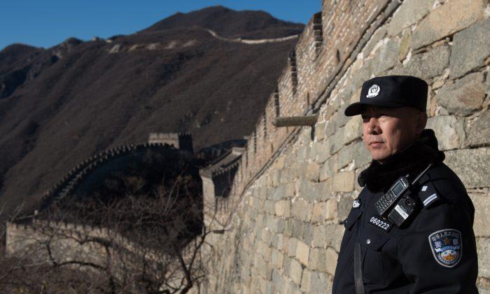 Un policía chino certa de la Gran Muralla China en las afueras de Beijing, 10 de noviembre de 2017. (Nicolas Asfouri/AFP/Getty Images)
