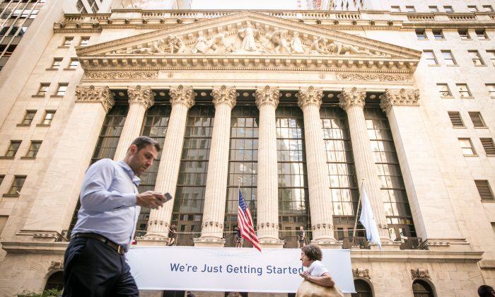Personas caminando por la Bolsa de Nueva York en el distrito financiero de Manhattan, el 26 de junio de 2017. (Crédito de Benjamin Chasteen / La Gran Época)