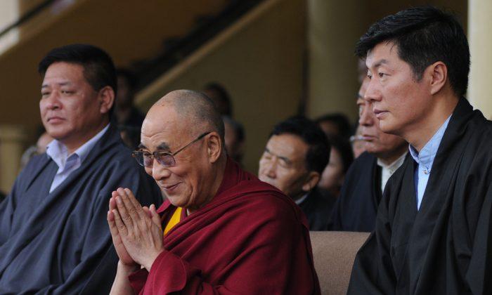 El líder espiritual tibetano Dalai Lama (C), flanqueado por el presidente de la Administración Central Tibetana, Lobsang Sangay (Derecha) y el presidente del Parlamento Tibetano en el exilio, Penpa Tsering (Izquierda), saluda a la audiencia durante el 52º aniversario del Día de la Democracia Tibetana en el templo Tsuglakhang en McLeod Ganj, Dharamsala, el 2 de septiembre de 2012. (STRDEL / AFP / GettyImages)