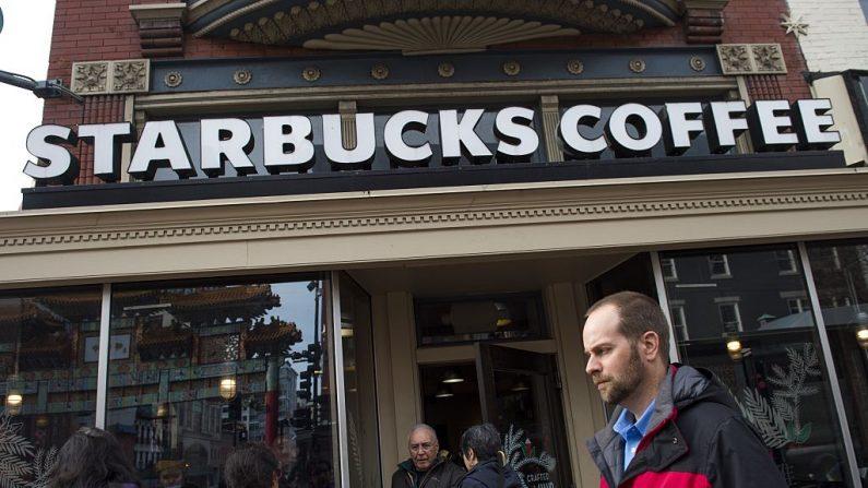 La gente pasa caminando frente a un local Starbucks en Washington, D.C., el 21 de diciembre de 2016. (Crédito de la foto debe ser SAUL LOEB / AFP / Getty Images)