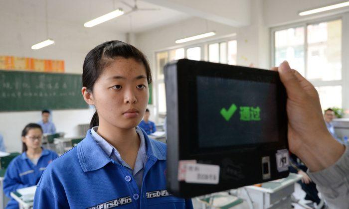 Un maestro utiliza una máquina de reconocimiento facial y de huellas dactilares para verificar a un estudiante antes de un examen de ingreso simulado a la universidad en la provincia de Hebei, en el norte de China, el 6 de junio de 2017. (STR/AFP/Getty Images)