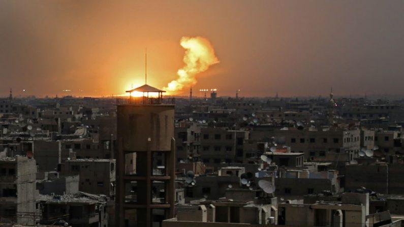 Una fotografía tomada el miércoles 28 de febrero de 2018 muestra llamas que estallan en el horizonte tras un ataque con cohetes en al-Shaffuniyah, en Ghouta Oriental, en las afueras de la capital siria-Damasco. (Crédito de AMMAR SULEIMAN / AFP / Getty Images)
