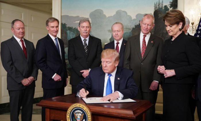 El presidente Donald Trump firma las sanciones comerciales contra China en la Sala de Recepción Diplomática de la Casa Blanca, en Washington, DC, el 22 de marzo de 2018. Estados Unidos impondrá aranceles de hasta 60 mil millones de dólares a los productos chinos como represalia contra el robo de propiedad intelectual estadounidense , dijo Trump. (MANDEL NGAN / AFP / Getty Images)