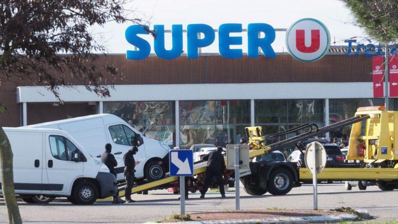 Los policías están trabajando afuera de un supermercado Super U en la ciudad de Trebes, en el sur de Francia, el 23 de marzo de 2018, luego de que fuerzas especiales mataran a un tirador que había tomado como rehenes a varias personas durante más de tres horas. (Crédito de RAYMOND ROIG / AFP / Getty Images)