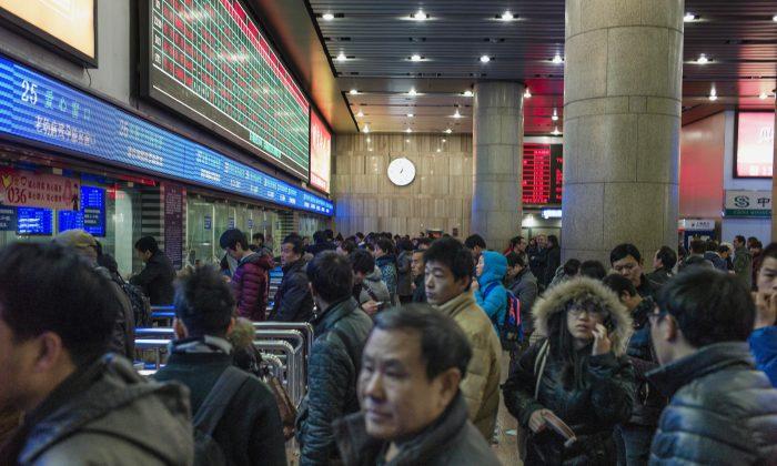 Pasajeros chinos hacen fila para comprar billetes de tren para regresar a sus casas para el Año Nuevo Lunar en la estación de trenes de Beijing, 4 de febrero de 2015. (Fred Dufour/AFP/Getty Images)