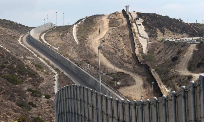 Las secciones nuevas y antiguas de la valla fronteriza de EE. UU.-México escalan una colina el 3 de octubre de 2013 cerca de San Diego, California. (John Moore / Getty Images)