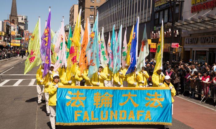 Los practicantes de la disciplina espiritual Falun Dafa, también conocida como Falun Gong, marchan en un desfile en Flushing, Nueva York, el 22 de abril de 2018. (Larry Dai/La Gran Época)