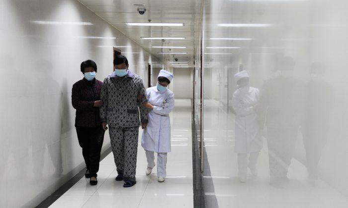 Un paciente con gripe aviar H7N9 camina por el pasillo de un hospital de la ciudad de Bozhou, en la provincia de Anhui, en el centro de China, el 19 de abril de 2013. Una reciente investigación interna del Partido Comunista Chino encontró una corrupción desenfrenada en el sistema médico de la provincia. (STR/AFP/Getty Images)