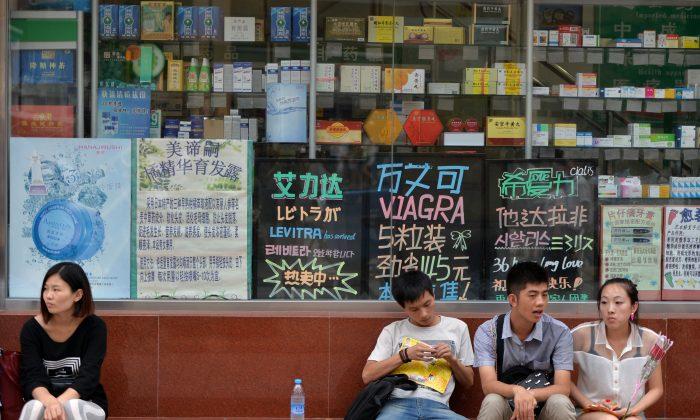 Clientes chinos esperan frente a una farmacia en Beijing, China, el 13 de agosto de 2013. China impuso aranceles elevados a los medicamentos importados, lo que dificultó que muchos ciudadanos pudieran seguir pagando el tratamiento de sus enfermedades. (Mark Ralston/AFP/Getty Images)