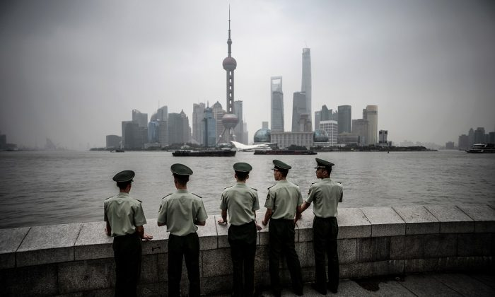Policías paramilitares parados frente al horizonte del distrito financiero de Lujiazui en Pudong, en el smog de Shangai, el 29 de septiembre de 2014. (JOHANNES EISELE/AFP/Getty Images)