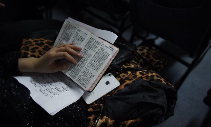 Un miembro de una iglesia clandestina sostiene una Biblia durante el culto de Nochebuena en un departamento en Beijing el 24 de diciembre de 2014. (Greg Baker/AFP/Getty Images)
