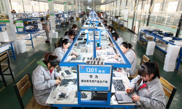 Los trabajadores chinos en una fábrica en Tengzhou, Shandong clasifican las piezas que se utilizarán para la fabricación de Huawei, el fabricante de equipos de telecomunicaciones más grande de China, el 1 de febrero de 2016. (STR/AFP/Getty Images)
