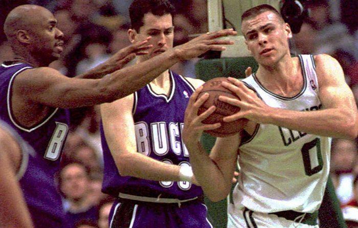 Los Boston Celtics Eric Montross (R) evaden el alcance de Milwaukee Bucks Vin Baker (L) mientras que los Bucks Marty Conlon (C) miran el 03 de marzo en el Boston Garden. Los Celtics ganaron 103-91. (COLOR KEY: Bucks wear purple.) AFP PHOTO (Photo credit should read JOHN MOTTERN/AFP/Getty Images)