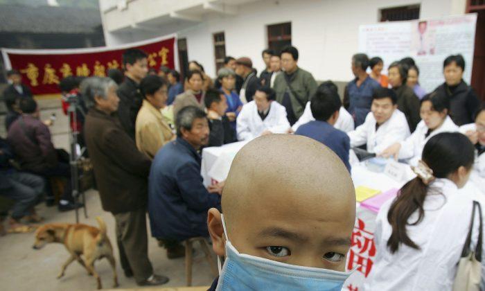 Un niño chino diagnosticado con leucemia utiliza una máscara mientras espera un chequeo médico por especialistas en cáncer en la localidad de Longshi, en la ciudad de Chongqing, China, el 2 de noviembre de 2004. (Fotos de China/Imágenes de Getty)