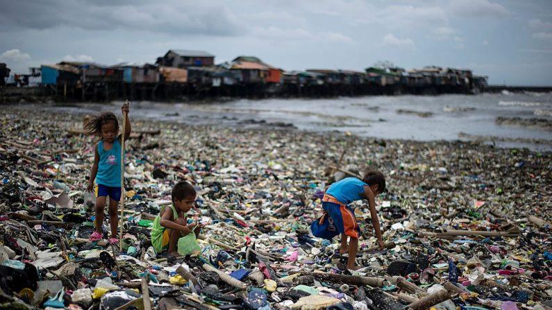 TOPSHOT - Los niños recogen botellas de agua de plástico entre la basura lavada en la costa como resultado de una ola de tormenta del tifón Haima en la Bahía de Manila el 20 de octubre de 2016. (NOEL CELIS/AFP/Getty Images)