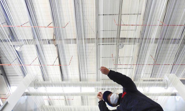 Foto tomada el 27 de febrero de 2018 que muestra a un empleado trabajando en una línea de producción de fibra de carbono T1000 en una fábrica en Lianyungang, en la provincia oriental de Jiangsu, China. El crecimiento de las fábricas de China se desaceleró nuevamente en febrero, ya que la producción y los pedidos de exportación cayeron debido a las fiestas del Año Nuevo Lunar, alcanzando su nivel más bajo en 19 meses, según los datos oficiales publicados el 28 de febrero. AFP PHOTO / - - / China OUT (El crédito de la foto debe leer -/AFP/Getty Images)