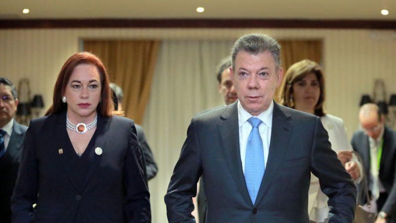 El presidente colombiano Juan Manuel Santos (izq.) y la ministra de Relaciones Exteriores de Ecuador, María Fernanda Espinosa, se van después de una reunión para discutir el caso del equipo de periodistas asesinados en Ecuador, al margen de la Cumbre de las Américas, en Lima, el 13 de abril de 2018. El presidente de Ecuador, Lenin Moreno, confirmó la muerte de tres miembros de un equipo de periodistas secuestrados por rebeldes renegados colombianos y lanzó una operación militar de represalia en la zona donde fueron secuestrados. FOTOGRAFÍA DE AFP / Luka GONZALES (El crédito de la foto debe leer LUKA GONZALES/AFP/Getty Images)  Traducción realizada con el traductor www.DeepL.com/Translator