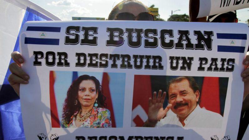 Un manifestante sostiene un cartel que representa al mandatario nicaragüense Daniel Ortega y a su esposa, la vicepresidenta Rosario Murillo, en el que se lee: 'Se busca por destruir un país'. Recompensa: Una Nicaragua Libre' durante la'Caminata por la Paz y el Diálogo', donde muchos demandan la renuncia de Ortega y Murillo. (Foto de Inti OCON / AFP) (El crédito de la foto debe leer INTI OCON/AFP/Getty Images)