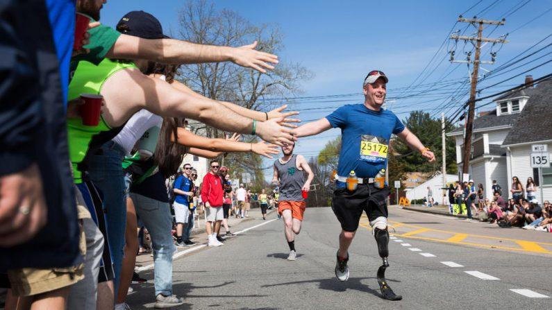 Los espectadores le chocan la mano a un corredor discapacitado mientras pasa la marca de las 6 millas del Maratón de Boston el 17 de abril de 2017 en Framingham, Massachusetts. (Kayana Szymczak/Getty Images)