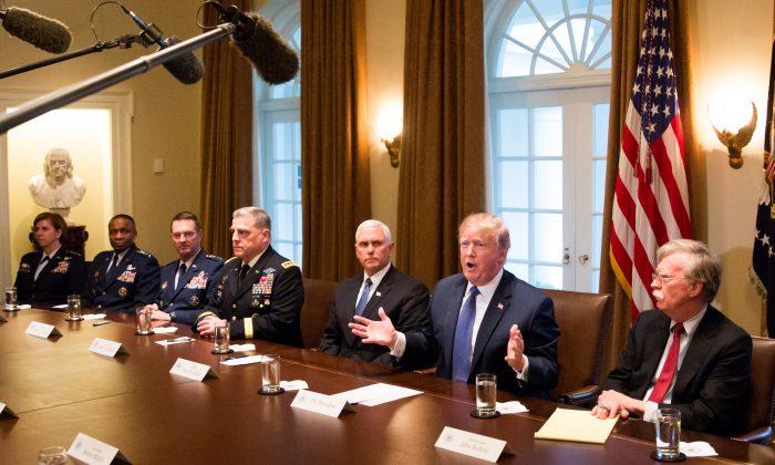 El presidente Donald Trump habla durante una reunión con altos líderes militares mientras está flanqueado por el vicepresidente Mike Pence (Iz) y el asesor de seguridad nacional John Bolton (Der) en la sala del gabinete de la Casa Blanca en Washington el 9 de abril de 2018. (Samira Bouaou / La Gran Época)