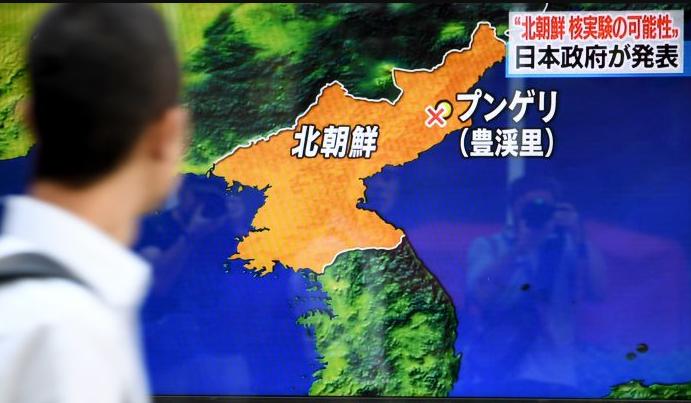 Peatones caminan frente a una pantalla de televisión transmitiendo un programa de noticias sobre la prueba nuclear de Corea del Norte, en Tokio-Japón, el 3 de septiembre de 2017. (Toshifumi Kitamura / AFP / Getty Images)