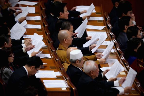 Un delegado monje budista invitado especial (Centro) lee el informe del Comité Central del Partido Comunista de China durante la sesión de clausura del 18º Congreso Nacional del Partido Comunista de China (PCCh) en el Gran Salón del Pueblo en Beijing, China, el 14 de noviembre de 2012. (Feng Li/Getty Images)