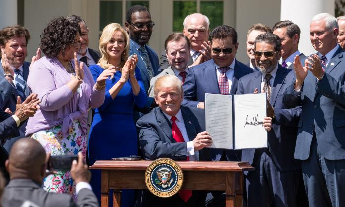 """El presidente Donald Trump firma la Orden Ejecutiva titulada """"Establecimiento de una Iniciativa de Fe y Oportunidad de la Casa Blanca"""" en el Día Nacional de Oración, en el Jardín de Rosas de la Casa Blanca, en Washington, el 3 de mayo de 2018. (Samira Bouaou/La Gran Época)"""
