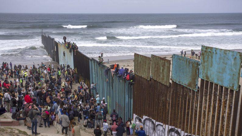 Personas escalan una sección de la cerca fronteriza para mirar a Estados Unidos cuando una caravana de solicitantes de asilo centroamericanos llega a la frontera en Tijuana, México, el 29 de abril de 2018. (David McNew / Getty Images)