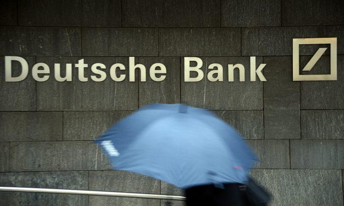 Una mujer con un paraguas pasa por delante de una sucursal del Deutsche Bank en Frankfurt am Main, el 29 de enero de 2013. La inversión china en el banco alemán no ayudó y una fusión con un banco estadounidense podría ser una mejor solución. (Thomas Lohnes/Getty Images)