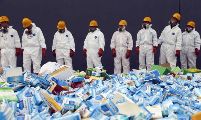 Trabajadores chinos se preparan para destruir medicinas falsas incautadas en Beijing, el 14 de marzo de 2013. Las empresas chinas dominan cada vez más la fabricación del mercado farmacéutico mundial, un desarrollo que plantea problemas de seguridad nacional en los Estados Unidos y en otros lugares. (STR/AFP/Getty Images)