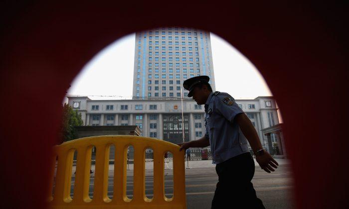Un policía pasando cerca de los tribunales de la ciudad de Jinan, China, 22 de agosto de 2013. (Feng Li/Getty Images)