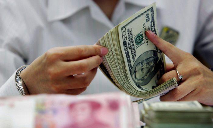 Una cajera de un banco cuenta los dólares estadounidenses y los yuanes en un banco en Shanghai, China, el 22 de julio de 2005. (STR/AFP/Getty Images)