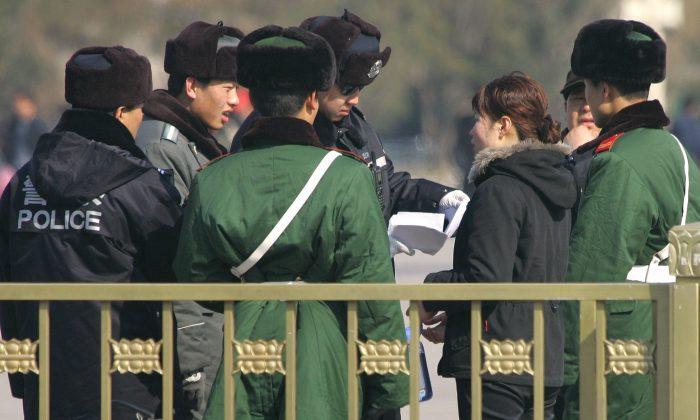 La policía y los guardias paramilitares rodean a una mujer mientras un policía lee su petición en medio de una reforzada seguridad en la Plaza de Tiananmen en Beijing, el 6 de marzo de 2007. (Frederic J. Brown/AFP/Getty Images)