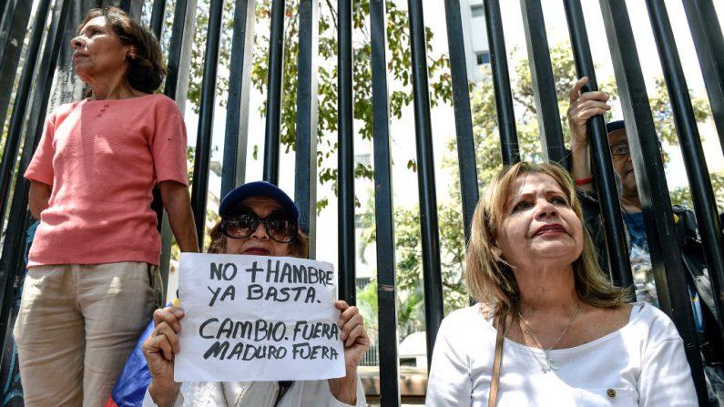 """Ciudadanos venezolanos de la oposición participan en una asamblea callejera en Caracas el 10 de mayo de 2018. Una coalición de grupos de oposición venezolanos organizó concentraciones en todo el país el sábado 20 de mayo para protestar por las elecciones presidenciales que considera fraudulentas y para exigir elecciones """"libres y transparentes"""" en una fecha futura. FOTOGRAFÍA DE AFP / JUAN BARRETO (El crédito de la foto debe leer JUAN BARRETO/AFP/Getty Images)  Traducción realizada con el traductor www.DeepL.com/Translator"""