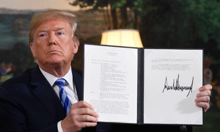 El presidente Donald Trump firma un documento que restablece las sanciones contra Irán después de anunciar EE.UU el abandono del acuerdo nuclear con Irán, en la Sala de Recepción Diplomática de la Casa Blanca en Washington, D.C., el 8 de mayo de 2018. (SAUL LOEB/AFP/Getty Images)