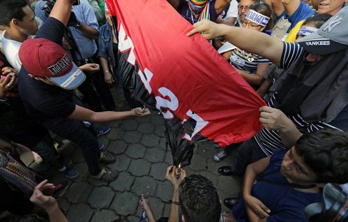 Manifestantes queman una bandera del Frente Sandinista de Liberación Nacional (FSLN), del grupo guerrillero que comandaba el actual mandatario Daniel Ortega. (Foto de INTI OCON / AFP) (El crédito de la foto debe leer INTI OCON/AFP/Getty Images)