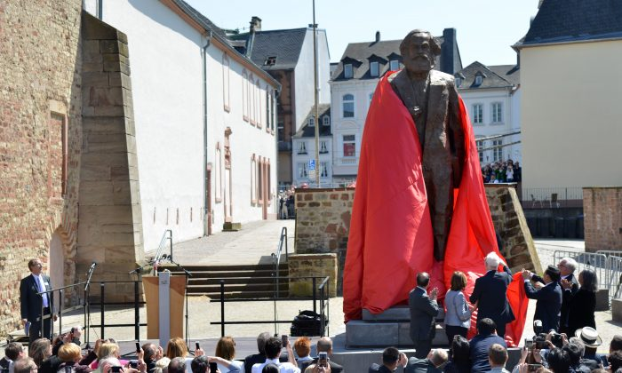 Visitantes observan mientras una estatua del pensador comunista alemán Karl Marx es develada el 5 de mayo de 2018 en su ciudad natal, Trier, al sudoeste de Alemania. (HARALD TITTEL/AFP/Getty Images)