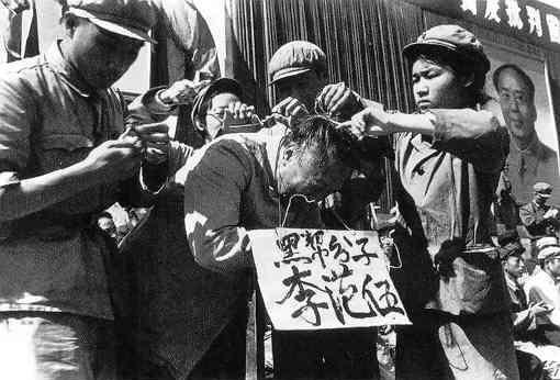 """Cuadros del Partido Comunista cuelgan una pancarta en el cuello de un hombre chino durante la Revolución Cultural de 1966. Las palabras en la pancarta dicen el nombre del hombre y lo acusan de ser miembro de la """"clase negra"""". (Dominio Público)"""