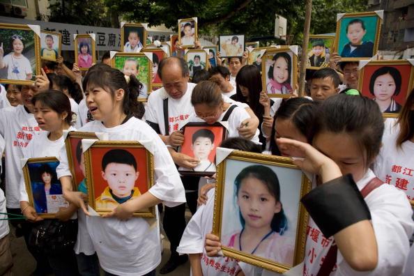 """Padres de alumnos fallecidos por el terremoto del 12 de mayo que causó el derrumbe de la escuela primaria de Xinjian  lloran desconsolados mientras sostienen retratos de sus seres queridos durante la conmemoración del Día del Niño en el campus de la escuela reducida en escombros el 1 de junio de 2008 en Dujiangyan, provincia de Sichuan, China. Cientos de padres y familiares de alumnos fallecidos usaron remeras con el lema """"Castigar severamente la corrupción y la construcción de mala calidad"""" durante la emotiva reunión. (Andrew Wong/Getty Images)"""