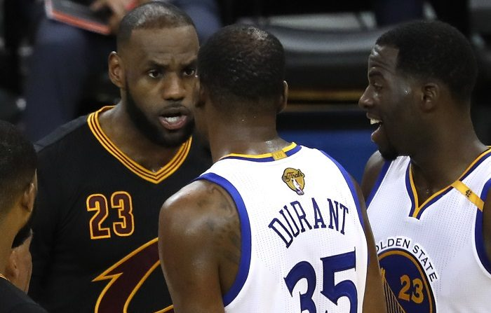El jugador Golden State Warriors Kevin Durant (c) y el jugador de Cleveland Cavaliers LeBron James (i) intercambian palabras en la cancha durante un partido de la NBA. EFE/Archivo