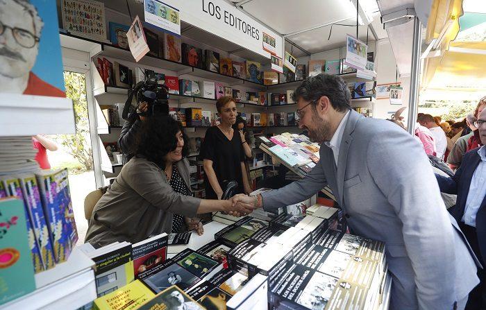 """El cómic presume de """"lectores polivalentes"""" en la Feria del Libro de Madrid El ministro de Cultura y Deportes, Maxim Huerta (d), saluda a la escritora Almudena Grandes (i), durante su visita a la Feria del Libro en el madrileño parque de El Retiro. EFE"""