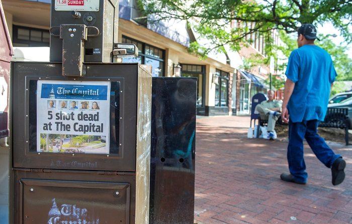 Un hombre camina junto a la edición de hoy del periódico de Annapolis Capital Gazette, cuya redacción fue víctima de un tiroteo este jueves que dejó cinco muertos, en Annapolis, Mary land (EE.UU), hoy, 29 de junio de 2018. EFE