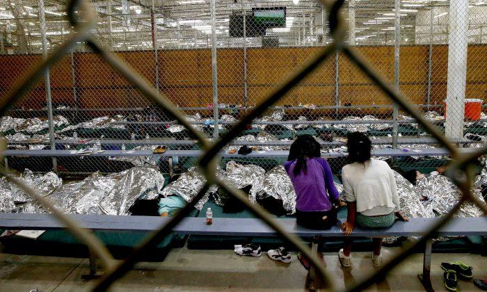 Dos niñas están sentadas en un área de espera, donde cientos de niños inmigrantes, en su mayoría centroamericanos, están siendo procesados y retenidos en el Centro de Internado de Nogales, del Servicio de Aduanas y Protección Fronteriza de Estados Unidos, el 18 de junio de 2014, en Nogales, Arizona. (Ross D. Franklin-Pool/Getty Images)