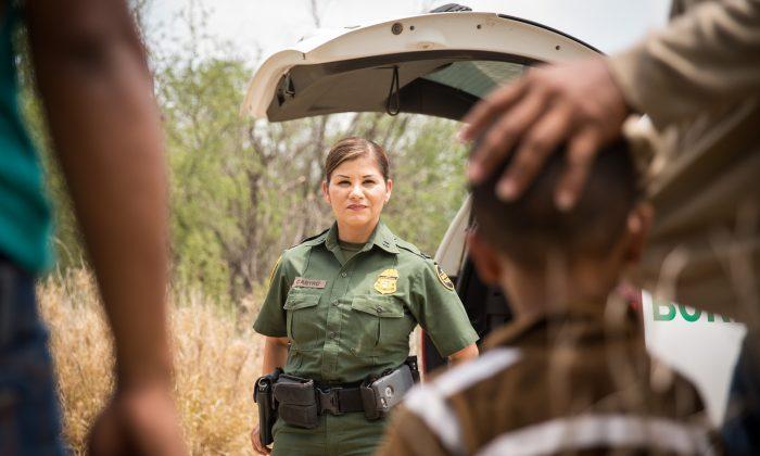 Marlene Castro, agente supervisora de la patrulla fronteriza, habla con un grupo de personas que cruzan ilegalmente la frontera, incluido un hombre con un niño, cerca del río Bravo en la frontera entre Estados Unidos y México en el condado de Hidalgo, Texas, el 26 de mayo de 2017. (Benjamin Chasteen / La Gran Época)
