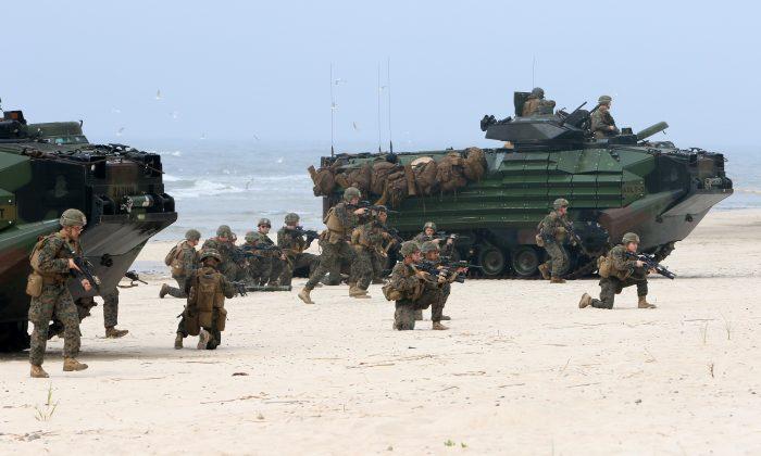 Soldados estadounidenses toman parte en un aterrizaje anfibio masivo durante las Operaciones bálticas de ejercicio (BALTOPS), un ejercicio multinacional militar centrado en el mar de la OTAN, el 4 de junio de 2018 en Nemirseta en el Mar Báltico en Lituania. (PETRAS MALUKAS / AFP / Getty Images)