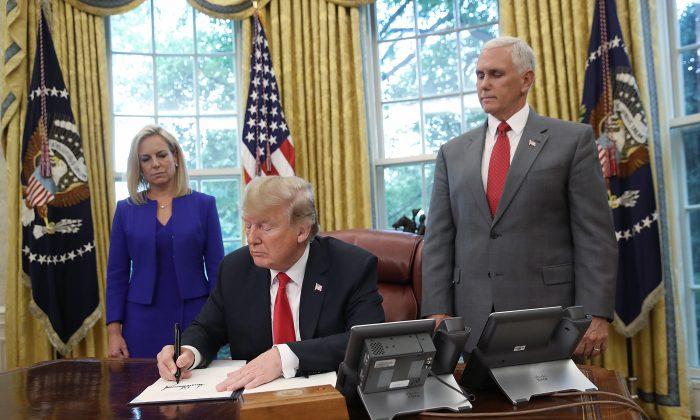 El presidente Donald Trump, acompañado por el secretario del Departamento de Seguridad Nacional Kirstjen Nielsen (Iz) y el vicepresidente Mike Pence (De), firma una orden ejecutiva que pondrá fin a la práctica de separar a familiares detenidos tras ingresar ilegalmente a Estados Unidos, en Washington el 20 de junio de 2018. (Win McNamee / Getty Images)