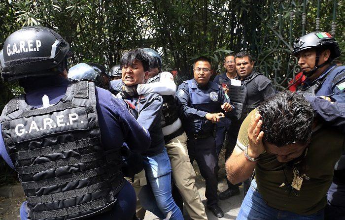 Dos hombres son detenidos por la policía, el 3 de julio de 2018, durante un enfrentamiento en un hotel donde militantes de un partido del candidato a la presidencia de México, aseguran haber hallado cientos de actas electorales apócrifas que supuestamente favorecen a otro candidatos, en Puebla (México). EFE/ Hilda Rios
