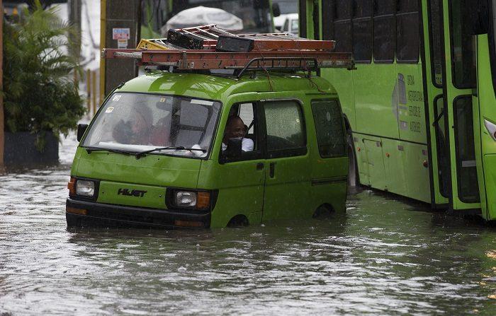 Decenas de barrios de la República Dominicana están hoy inundados por las torrenciales lluvias que caen sobre gran parte del país a causa de una onda tropical asociada a los remanente de la degradada tormenta Beryl. EFE/Orlando Barría