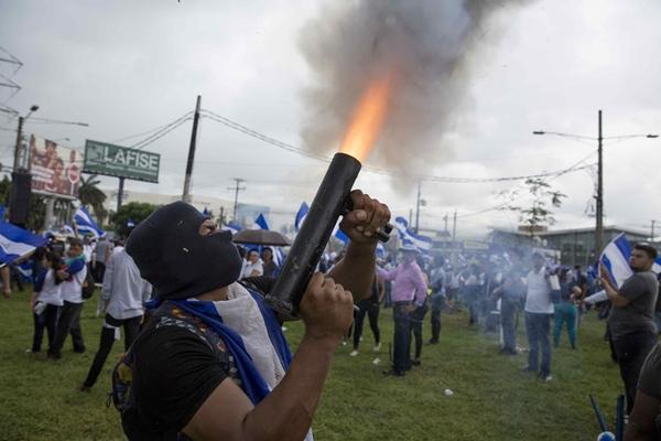 """Un joven lanza un mortero durante la marcha """"Juntos Somos Un Volcán"""", jueves 12 de julio de 2018, en el día número 86 de protestas con el gobierno de Daniel Ortega, en Managua (Nicaragua). La multitudinaria marcha comenzó la capital de Nicaragua en rechazo al presidente Daniel Ortega, a quien diversas organizaciones humanitarias responsabilizan por la muerte de al menos 351 personas en menos de tres meses. EFE/Jorge Torres"""
